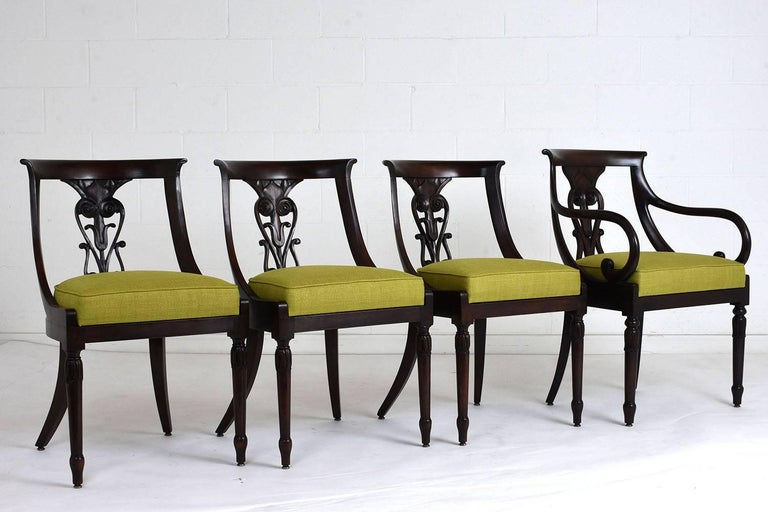 This Antique Set of Four Hollywood Regency-style Dining Chairs has been handcrafted out of mahogany wood stained in deep mahogany color with a polished finish and is fully restored. The set features three side chairs, an armchair, and the seats have