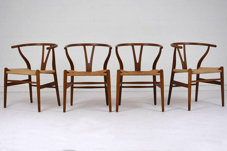 This set of four 1970s Mid-Century Modern-style dining chairs feature teak wood frames stained in a light walnut color and a polished finish. The horseshoe backs have a V-shaped splat and serpentine arms. The round tapered legs have stretched bars