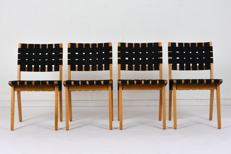 This set of four 1950s dining chairs are made in the style of Klaus Grabe. The wood frames have geometric designs and are finished in a natural color stain. The chairs have square backs and tapered legs. The comfortable seats feature black nylon