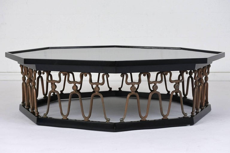 This 1980s Hollywood Regency-style octagonal coffee table is made of wood stained in a deep black color with a lacquered finish. The top of the table is accented by a lip at the edge. The base of the table features a gilt metal repetitive pattern