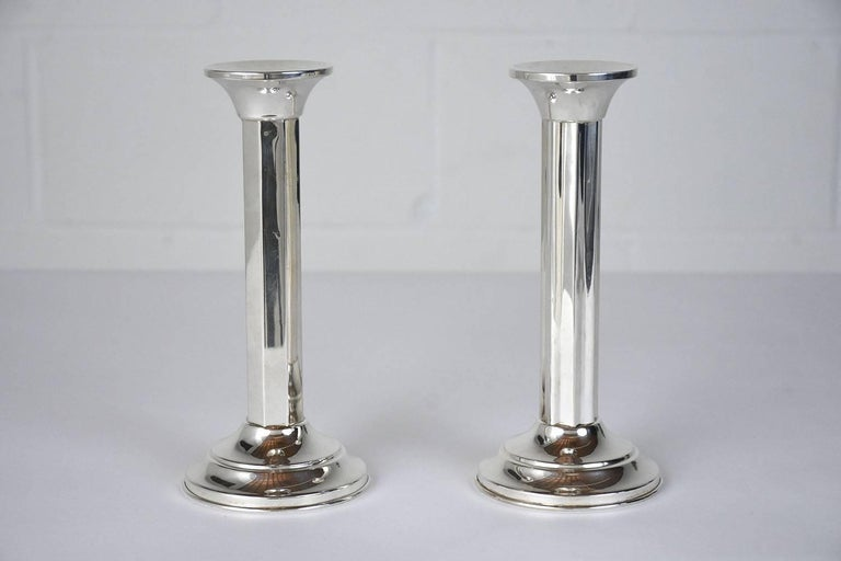 This pair of 1920s Art Deco-style candleholders is made from sterling silver stamped .800. The candle holders have a Classic design with faceted sides and a rounded base. This pair of candle holders is sturdy, elegant, and ready to be used in any