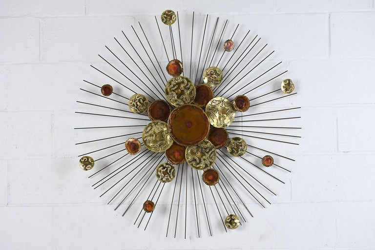 This 1970s Midcentury-style starburst wall sculpture is made by C. Jere. The sculpture features brass gold and reddish color medallions etched with different designs. The medallions are placed on top of one another in varying patterns. Around the
