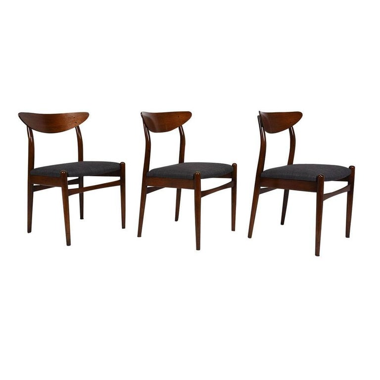 This set of six 1960's Danish Mid-Century Modern-style dining chairs feature teak wood frames that have been stained a beautiful dark walnut color. The carved frames have a unique boomerang shaped seat back and four stretched tapered legs. The
