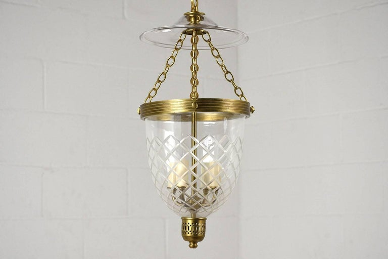 This 2000s Regency-style pendant light features a brass base. The brass base and chain is accented by an etched glass surround. Inside there are four lights in working condition. The lights can have 15 to 45 Watt bulbs. This pendant light is sturdy,