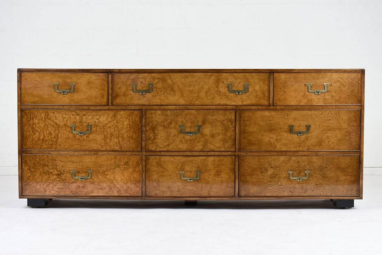 This 1960s modern style chest of drawers is made by John Widdicomb. The nine-drawer chest is covered in birch wood veneers stained in a rich light walnut color and a lacquered finish. The drawers have a delicate moulding accent along the edges with