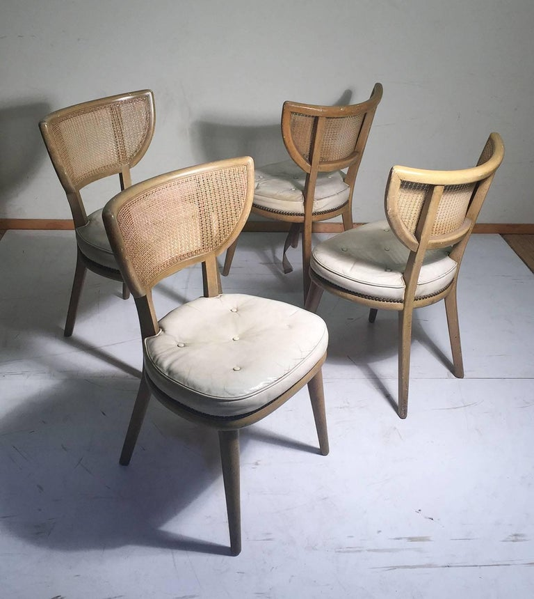 Vintage set of four American Mid-Century Modern chairs in the manner of William Haines, Paul Laszlo and Edward Wormley for Dunbar.   These are really ready for refurb. The seats were done on white leather and may be of interest to preserve. Rattan