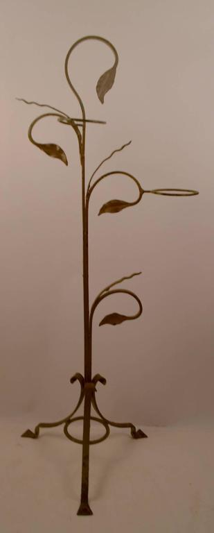 Wrought iron freestanding plant stand by Salterini. This example hold two flower pots, and is in old tan paint finish, paint shows wear, normal and consistent with age.