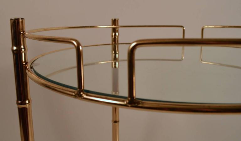 Diminutive circular two-tier rolling serving, bar cart with glass shelves. Brass faux bamboo structure, Hollywood Regency style, very fine original condition. Height to top shelve 26