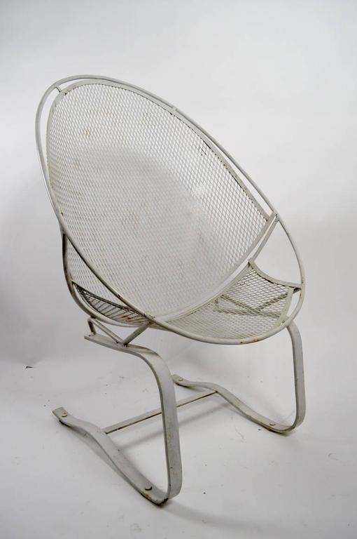 Classic Salterini high back cantilevered metal mesh and steel rod chair. This example is in white finish, which shows minor cosmetic wear. No damage, welds, or repairs. Suitable for indoor or outdoor use.