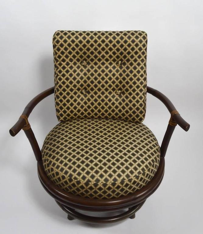 Pair of unusual bamboo swivel chairs. Original darkened finish, original upholstery, shows light wear, normal and consistent with age.