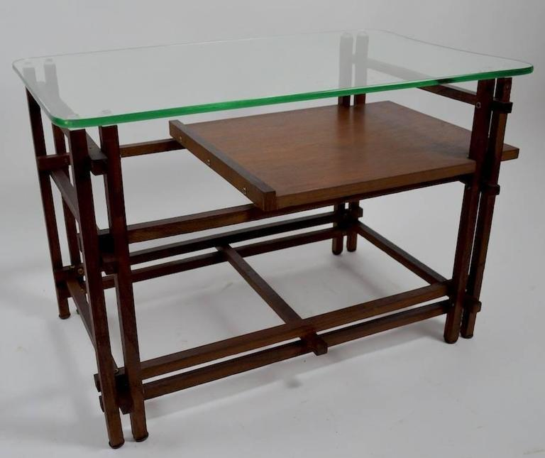 Pair of architectural wood and glass tables, after Henning Norgaard, for Komfort.   Both are in very good, original condition, showing only minor cosmetic wear, normal and consistent with age. Original shaped plate glass tops rest on squared wood