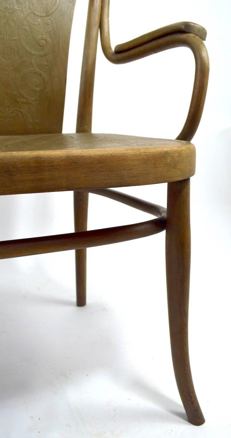 Unusual bentwood settee, bench by Thonet. This example has an embossed pressed wood back and seat, the finish is weathered, the frame shows some wear including a glue repair to the back of the lower oval stretcher. Measures: Arm H 26.
