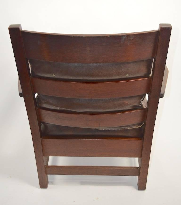 Nice Arts & Crafts Mission armchair by L.. & J.G. Stickley, in original finish, finish shows cosmetic wear, normal and consistent with age. The seat cushion is original, however has been recovered at some point, the back cushion is original. Chair
