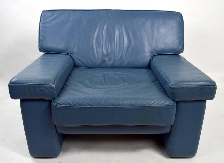 Nice pair of leather club chairs designed by Walter Knoll for Brayton International. Upholstered in greyish blue leather, which shows some cosmetic wear, and some Minor White paint (as shown) on surface. Nice comfortable and chic. Ottoman shown is