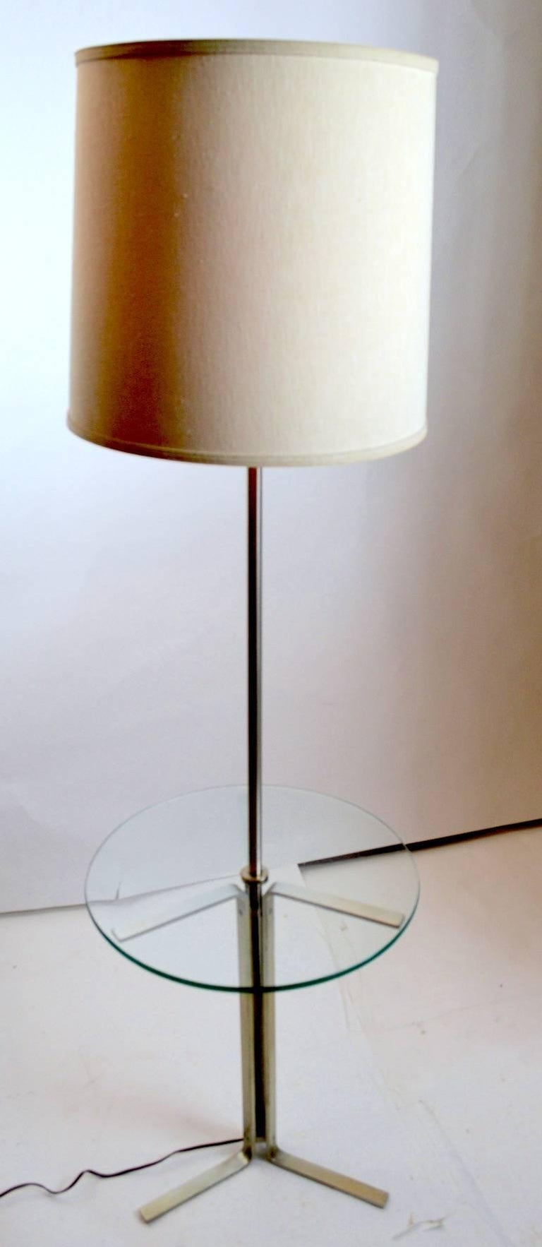 Modernist design and construction combination floor, table lamp. This example has an aluminium frame with a circular plate glass disk table surface. Table surface height 22 inches. Clean, working condition, shade not included.