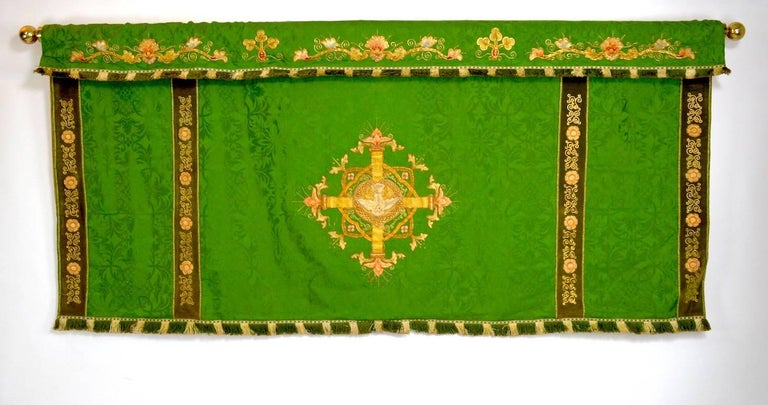 Interesting woven tapestry which hangs on a very heavy brass rod. The tapestry has a bird on a cross motif, fringe and decorative trim.