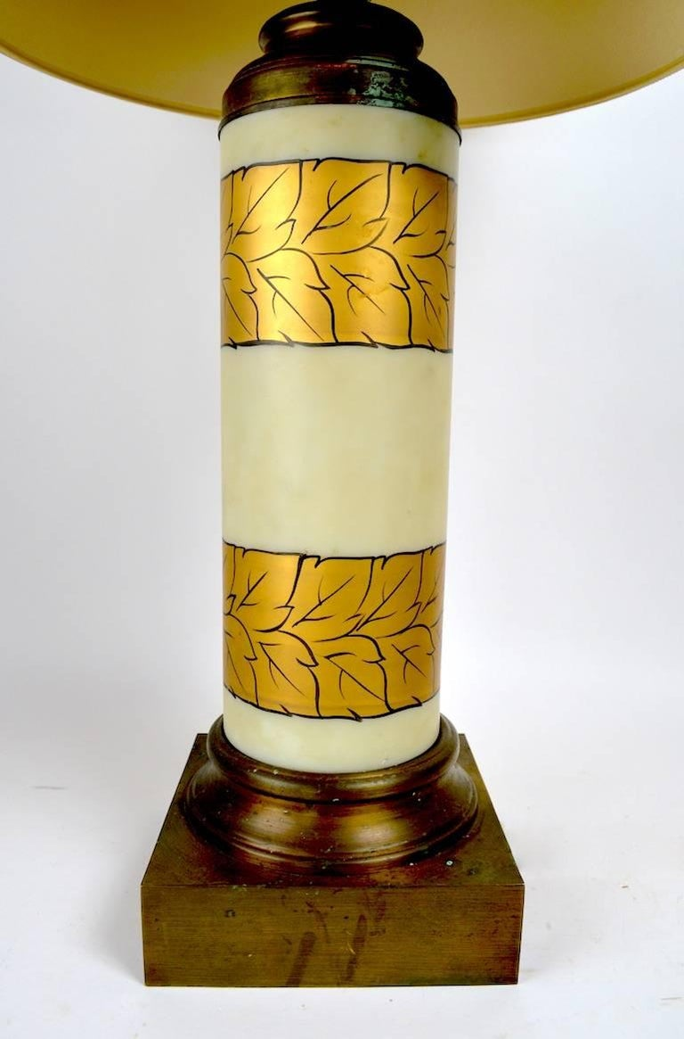 Cylindrical frosted white glass with gold foliate decoration, on brass bases. These lamps show some cosmetic wear and oxidation to the finish, notably on the bases and tops, as shown. Working, original condition, shades not included.
