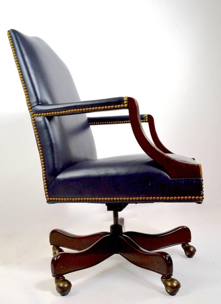 Classical style leather upholstered mahogany frame office, desk, executive chair by Hancock and Moore. Swivel, tilt model, arm height 27.5 inches seat height 18 inches. This example shows some signs of age and use, as shown.