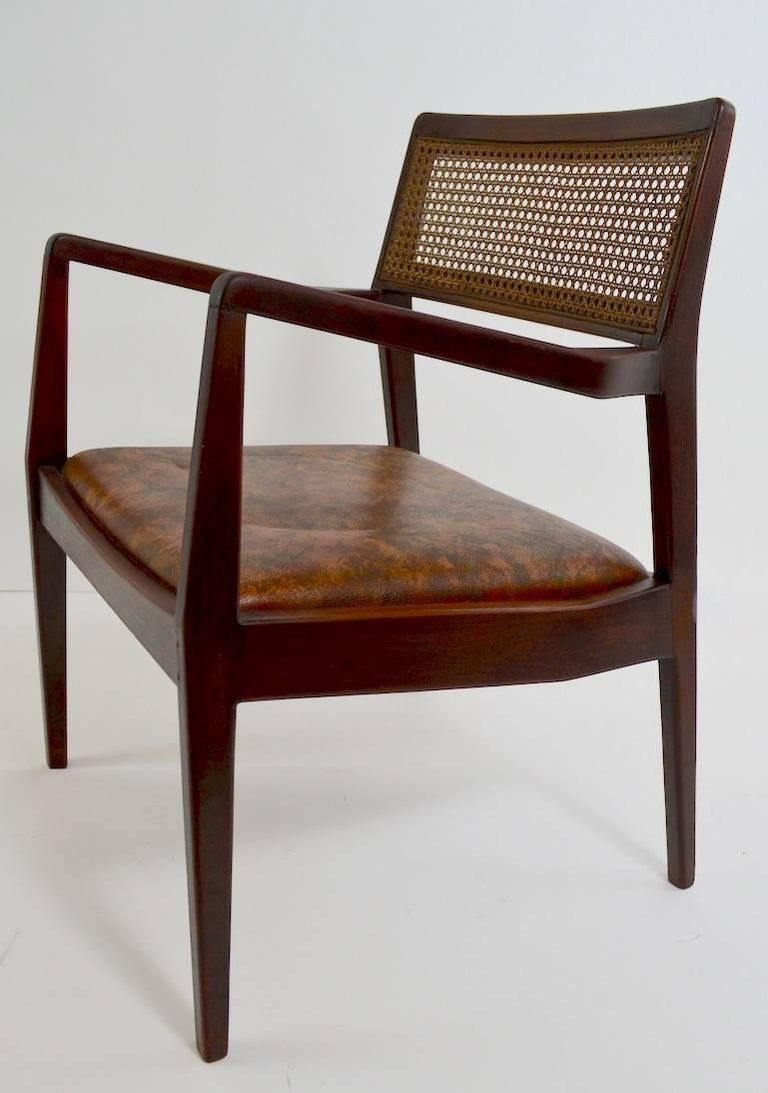 Walnut frames, caned backrests, and vinyl upholstered seats. This set consists of two arm chairs and four side chairs. The frames show some old repairs however are sturdy, solid and ready to use.