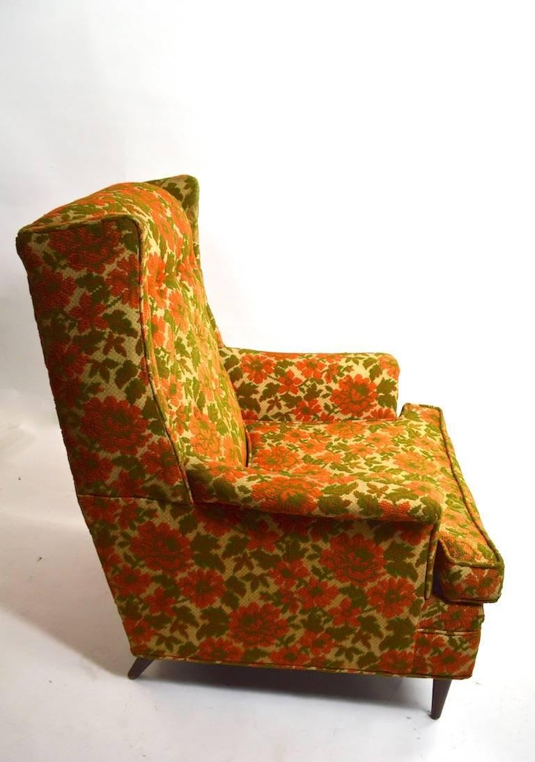 Large midcentury lounge chair in original floral tweed fabric. The lower seat cushion has hardened foam, and the foam must be replaced. Measures: Seat height 16.5, arm height 22 inches. Stylish lounge chair designed in the manor of Paul McCobb.