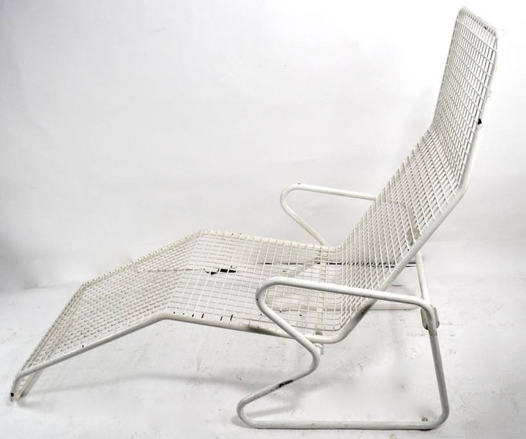 Two reclining metal chaise lounge chairs, made by Erlau AG of Germany, design attributed to Karl Fichtel. Each chaise has a metal grid body, tubular metal base, and green upholstered pad. Chair will recline back or sits in down position. Both show