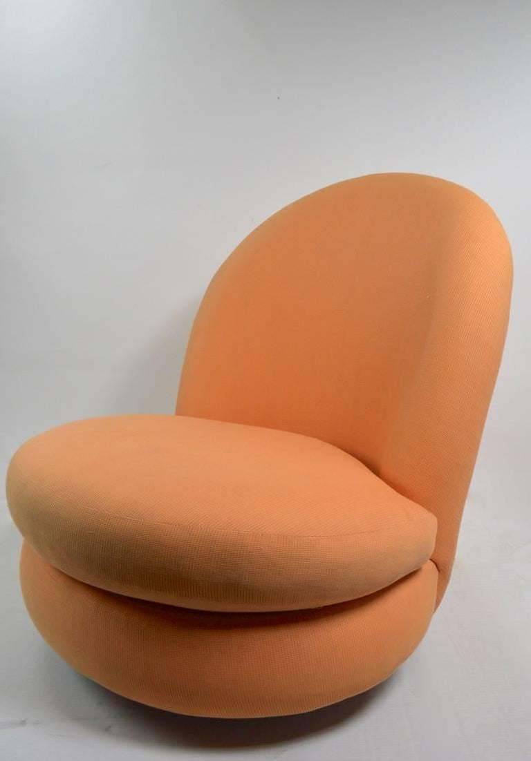 Stylish and chic, swivel tilt lounge chair designed by Milo Baughman for Thayer Coggin. Original peach upholstery, thick and heavy chrome disk base. Fabric usable as is, but shows cosmetic wear, including some staining etc, normal and consistent