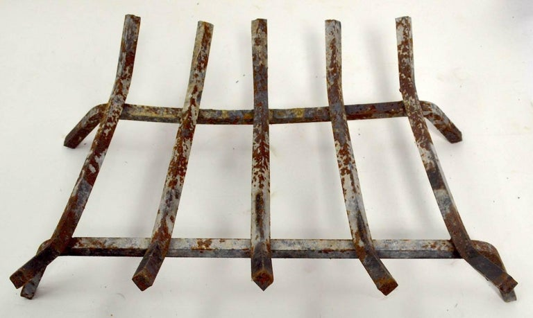 Wrought iron fireplace grate, log holder insert. Solid iron bars, on iron bar base, shows cosmetic wear, normal and consistent with age and use.