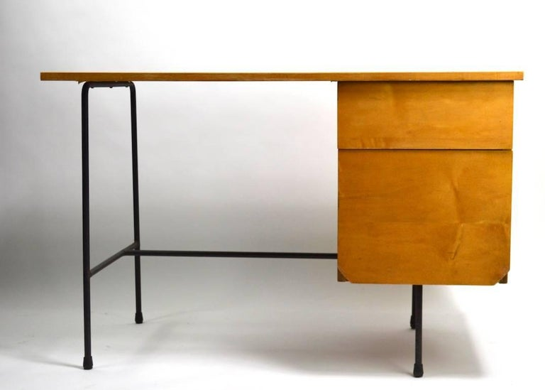Rare desk designed by Clifford Pascoe, selling with original desk chair. The desk has a faux wood Formica top, blonde wood drawers and black wrought iron legs. Two drawers, lower drawer is deeper than the top drawer. Dimensions for chair as follows