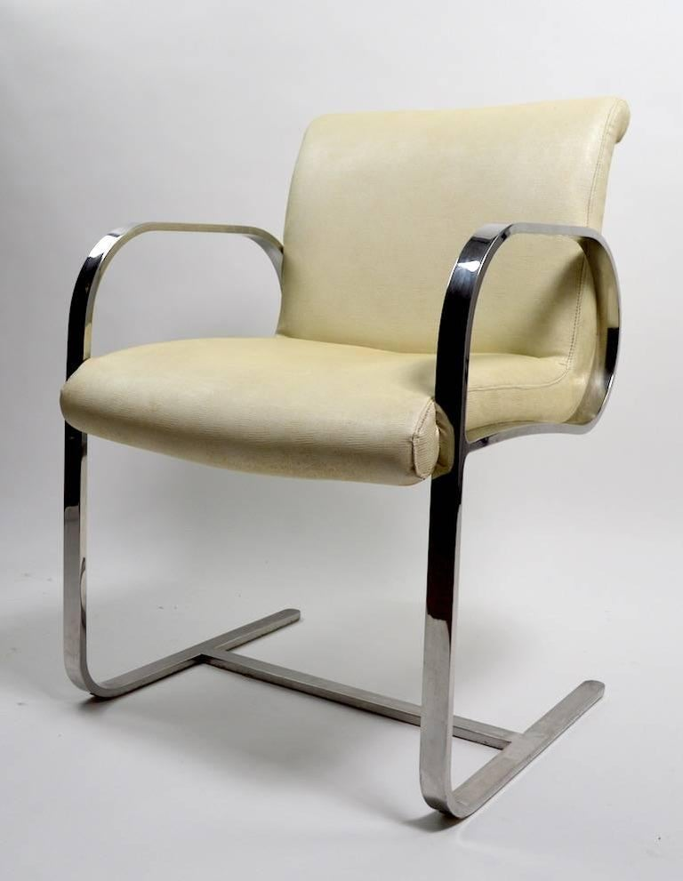 Pair of stylish armchairs attributed to Brueton, flat bar chrome frames support vinyl seats. Overall good condition, chrome shows cosmetic wear, specifically light scratching to the arm surface, no rust, or pitting, vinyl upholstery shows wear, as