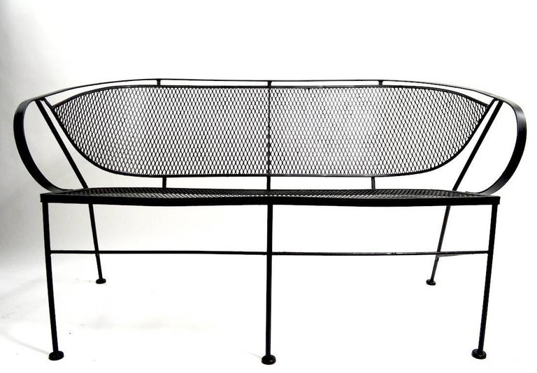 Stylish garden bench attributed to Woodard. This example is in very good condition, in recently painted black finish. Measures: Arm H 25 x Seat H 16.5 inches. Suitable for indoor and outdoor use.