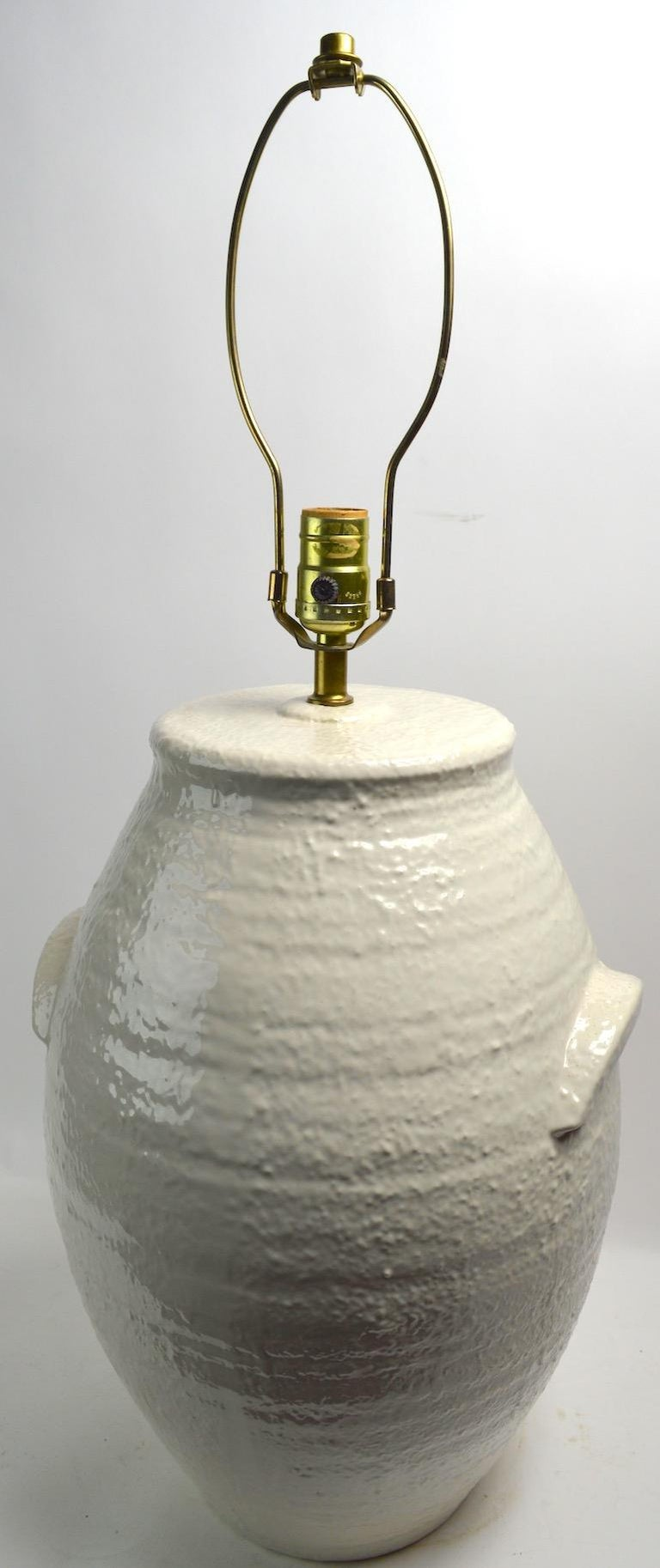 Pair of decorative off white ceramic lamps in the form of antique handled stoneware vessels. Textured high glaze surface and large scale make these a statement pair of lamps, circa 1970s-1980s. H to top of ceramic body 17 inches.