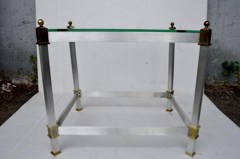 Elegant and stylish side tables with brushed aluminum and brass frames and thick plate glass tops. Both are in very good original condition, showing only light cosmetic wear to brass finish, normal and consistent with age. Tasteful design which can