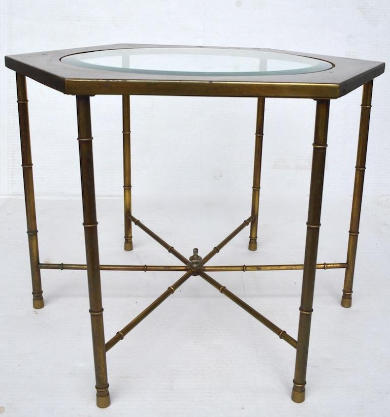 Decorative pair of hexagonal brass and glass tables with brass faux bamboo legs. Each table has a circular bevelled glass insert top, brass tops show minor cosmetic wear, normal and consistent with age.