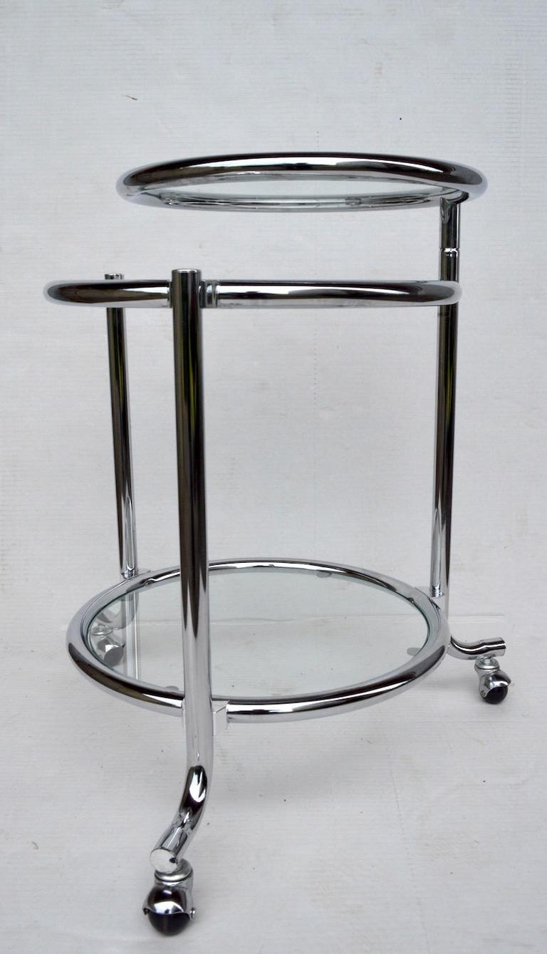 Stylish tubular chrome serving / bar cart with three chrome ring and glass tray surfaces. The top disk tray surface is adjustable, pivoting out from the centre post, as shown. Well made, and in very fine original condition, clean and ready to use.