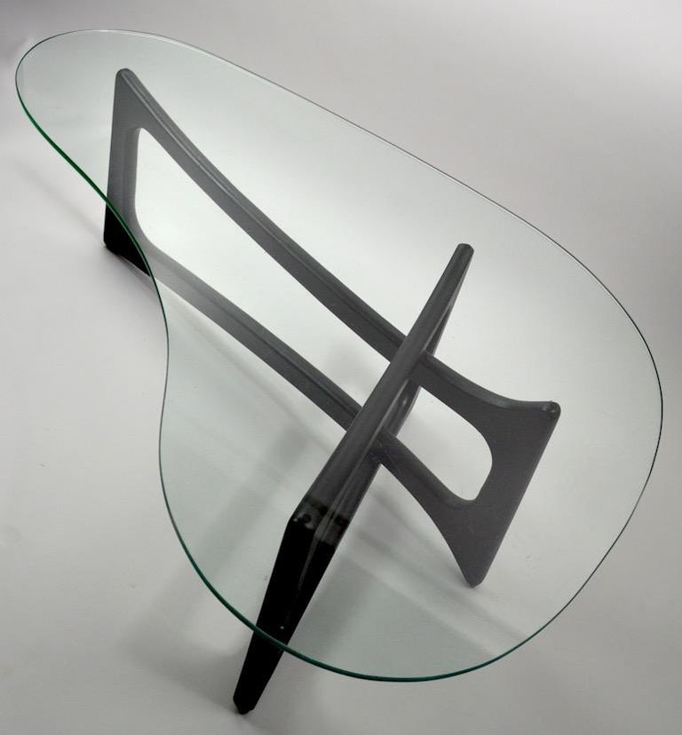Classic free-form glass top coffee table designed by Adrian Pearsall for Craft Associates. This example is in later black paint finish, the top shows inconsequential wear, normal and consistent with age. Stylish and chic midcentury glass top table