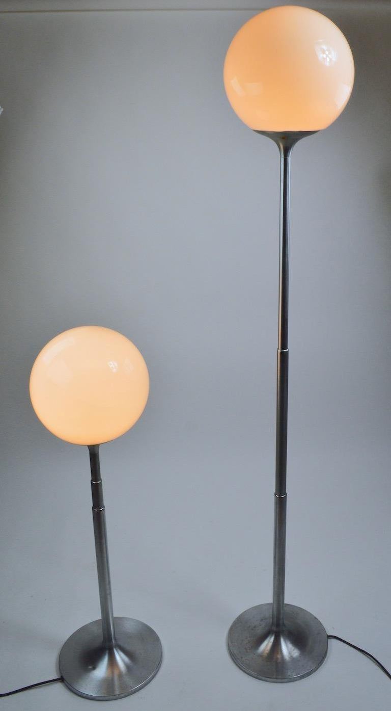 Rare and unusual pair of telescoping brushed steel floor lamps with glass ball globe tops. The lamps each have three concentric tubular tubes which can be extended or condensed to adjust the height. Lamps in totally extended position 70 inch H x