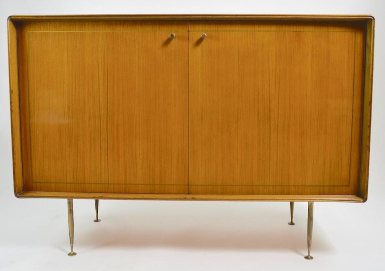 Chic and stylish two-door cabinet which opens to interior drawers, as shown. The case has shaped sculptural edges, tapered brass legs, brass pulls, and inlay brass trim. It is in original finish, which shows cosmetic wear normal and consistent with