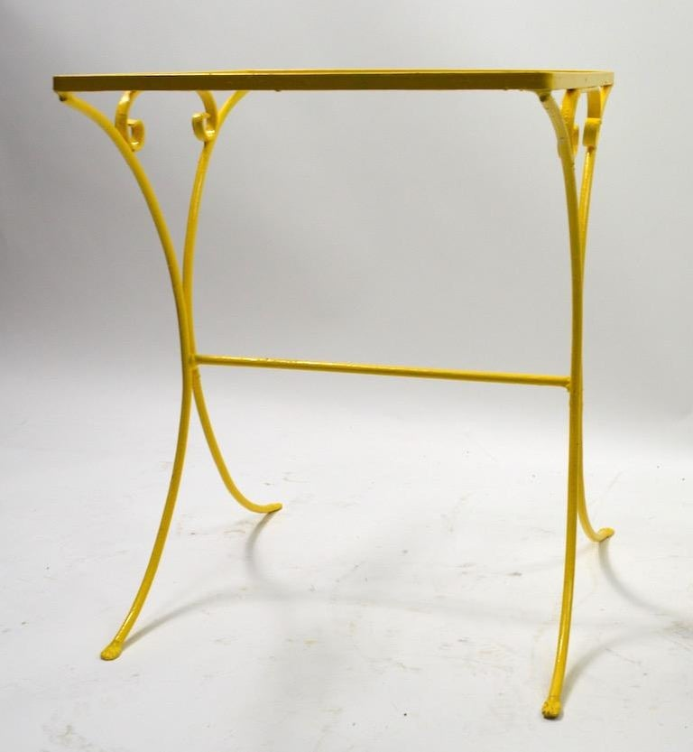 Stylish wrought iron table attributed to Salterini. Suitable for both indoor and outdoor use, currently in later yellow paint, selling without glass top.