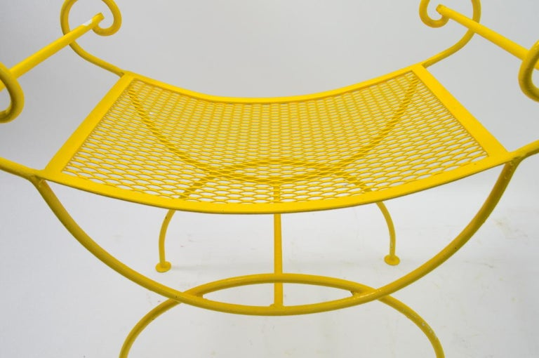 Stylish wrought iron bench, metal mesh seat, wrought iron rod frame. Currently in later sunshine yellow paint finish, shows minor wear and loss to paint finish. Attributed to Salterini, suitable for indoor and outdoor use, clean ready to use