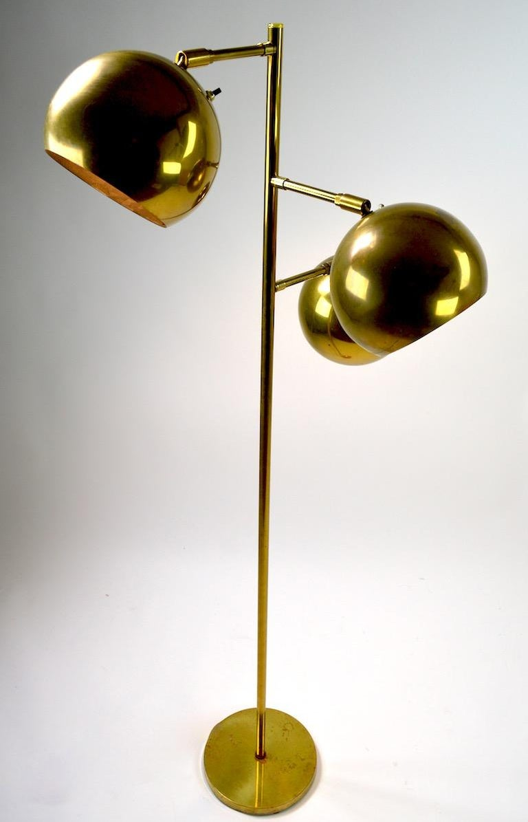 Three-light floor lamp in brass with ball form globe shades, which pivot to direct the light. Each shade has an on/off switch allowing independent operation of each light. Nice quality construction, brass finish shows some wear, and signs of age and