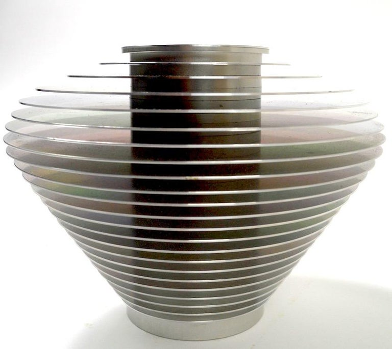 Saturn vase by Avedis Baghsarian constructed of stacked graduated aluminum rings surrounding a cylindrical aluminum core. This series was designed to come apart and be reassembled in almost infinite configurations. Original, clean condition, fully