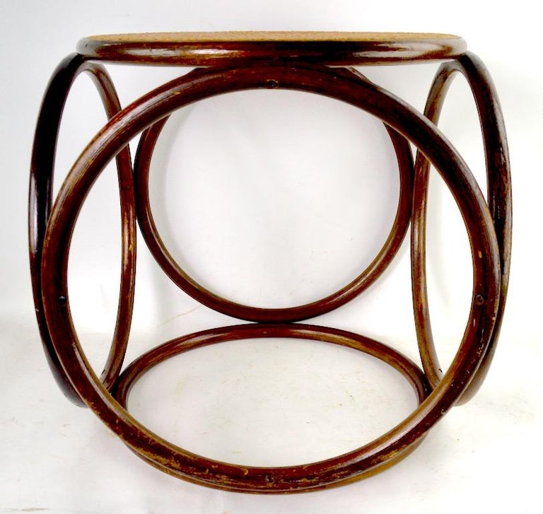 Classic Thonet stool having bentwood frame and caned seat, No structural damage, or breaks, finish shows cosmetic wear, normal and consistent with age.