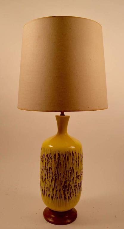 High glaze yellow ceramic lamp with red clay ground. Working, clean, original, mounted on original wood base, shade not included. Height to top of socket 28