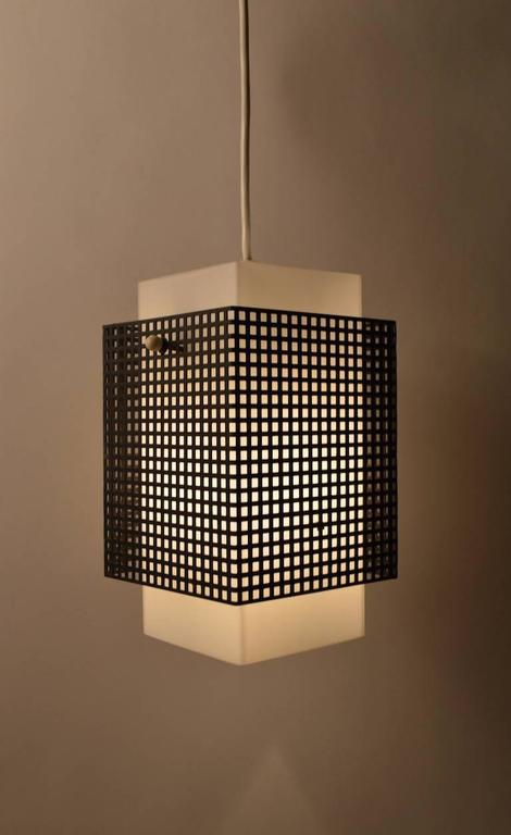 Perforated black metal shade surrounds white glass diffuser, suspended from white cord, original white plastic ceiling canopy included. Sophisticated European Minimalist design reminiscent of Sarfatti or perhaps Wirkkala. Outer metal shade 6.75