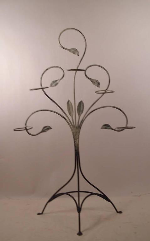 Wrought iron freestanding plant stand by Salterini. This example hold five pots, standing on tri part base, suitable for indoor or outdoor use.
