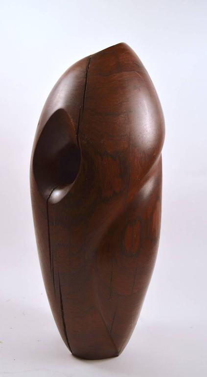 Impressive solid rosewood sculpture, organic form, with rich original patina. The freestanding oblong shape flows visually, with a sinuous top to bottom curve, and a hole that adds to the flow and life of the piece. Over the years, the wood has