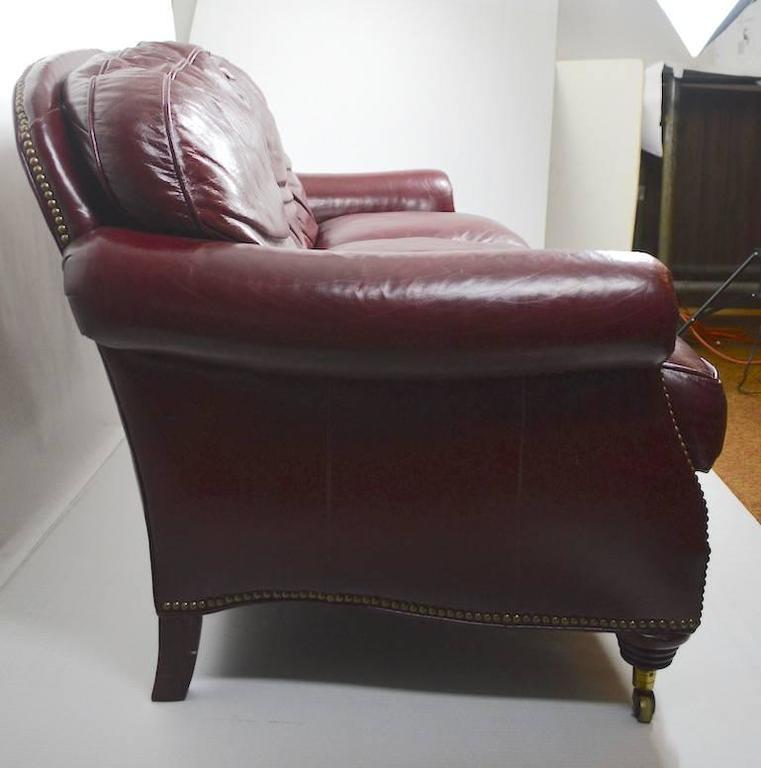 Comfy burgundy leather sofa, with brass studs. Classic form, original condition, clean, ready to use. Cushions do sit flat, they were just not placed correctly in the photo.