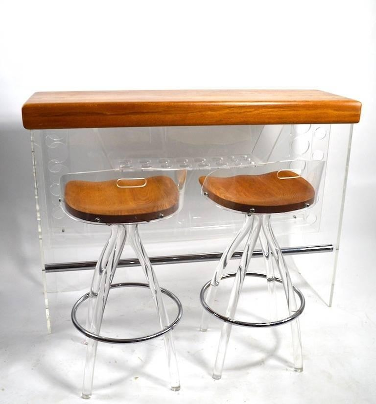Very chic Lucite bar with oak top, comes with two Lucite and wood stools. The bar has a hidden light under the top surface, the stools swivel to adjust seating position. Dimensions in the listing are for the bar, stool dimensions as follows.