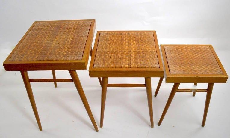 Unusual to find nesting table sets in pairs, two sets of three each tables. These tables are graduated in size, dimensions in listing are the largest of the three, they are cerused finished wood frames with grass mat weave tops. Both sets show minor