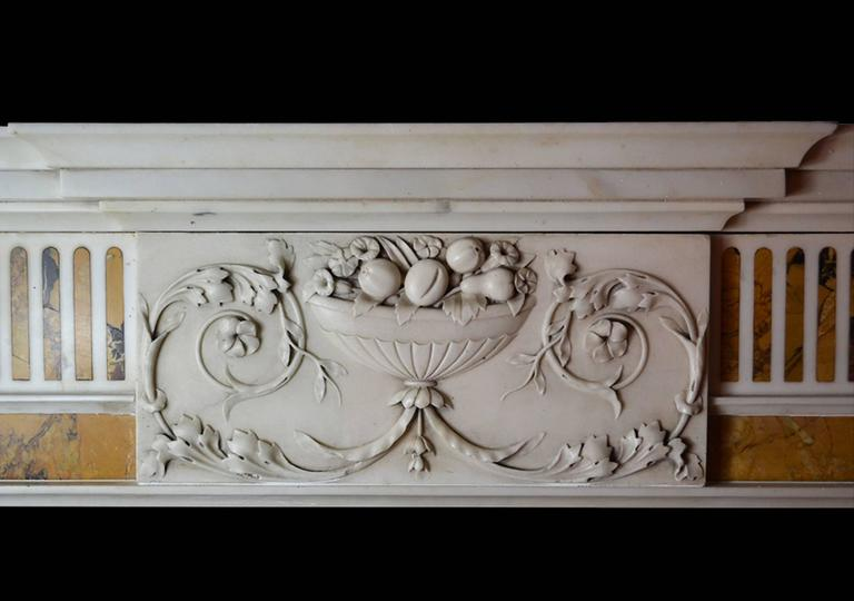 An elegant and well-proportioned late 18th century Irish chimneypiece in statuary marble GEO-ZE29, circa 1790. The chimneypiece has tapering pilasters inlaid with stop flutes of Convent Siena terminating beneath elongated corner blockings carved